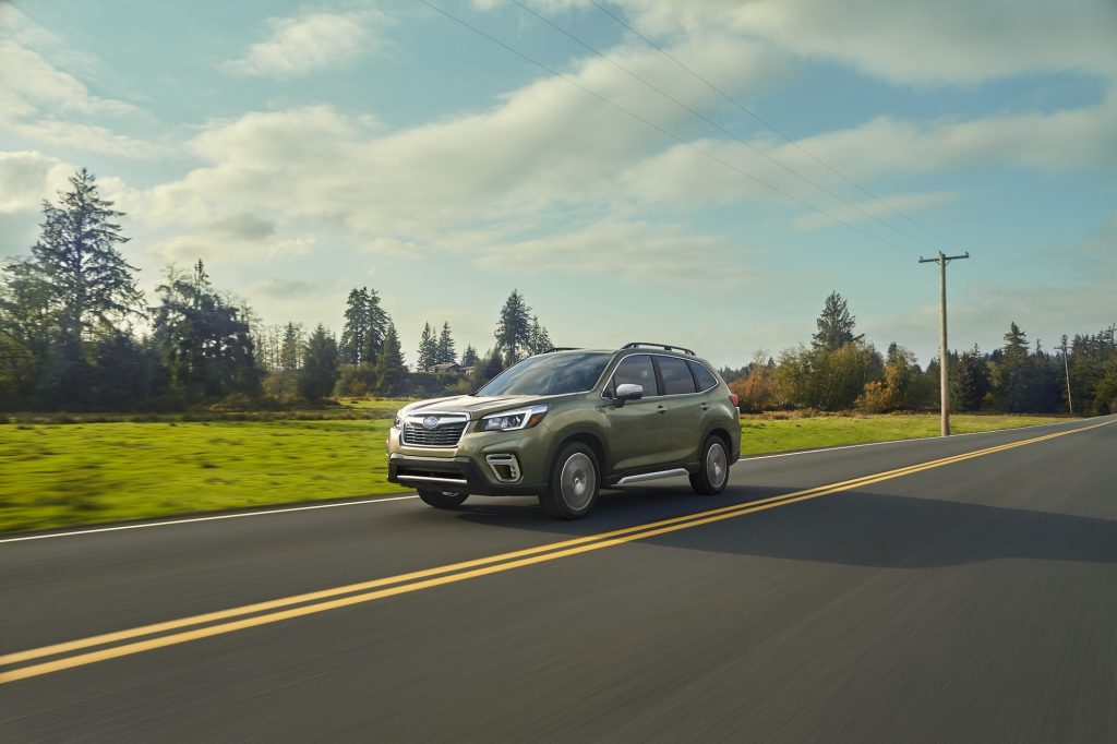 A sage-green 2020 Subaru Forester traveling on a two-lane highway past green grass and pine trees on a partly cloudy day, one of the safest compact SUVs recommended by Consumer Reports.