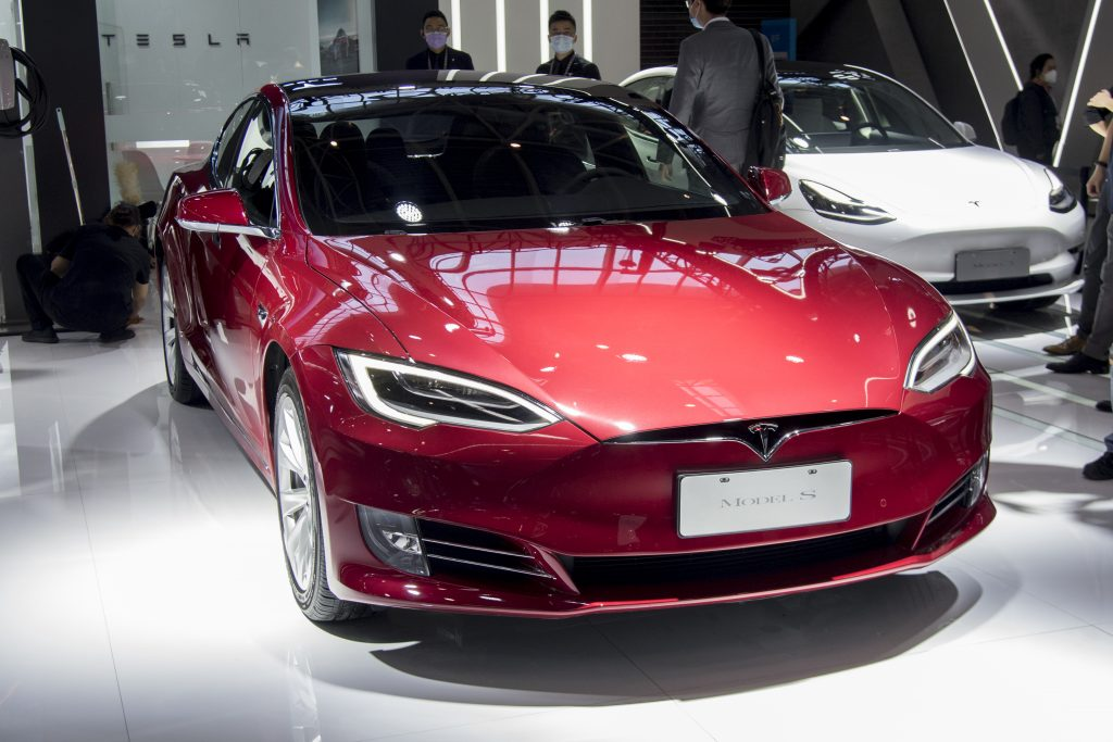 A shiny red 2020 Tesla Model S sits in the spotlight and is highlighted in Consumer Reports cars to avoid buying list.