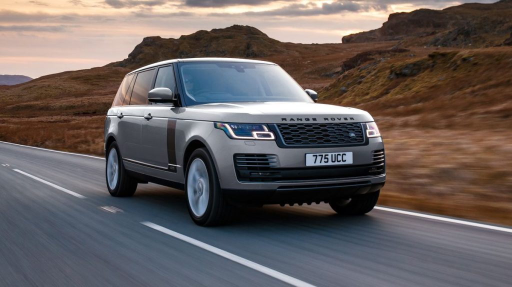 A 2020 Range Rover driving down the road in front of mountains