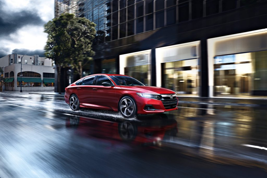 A red 2021 Accord Sport 2.0T midsize sedan travels on a wet city street on a cloudy day