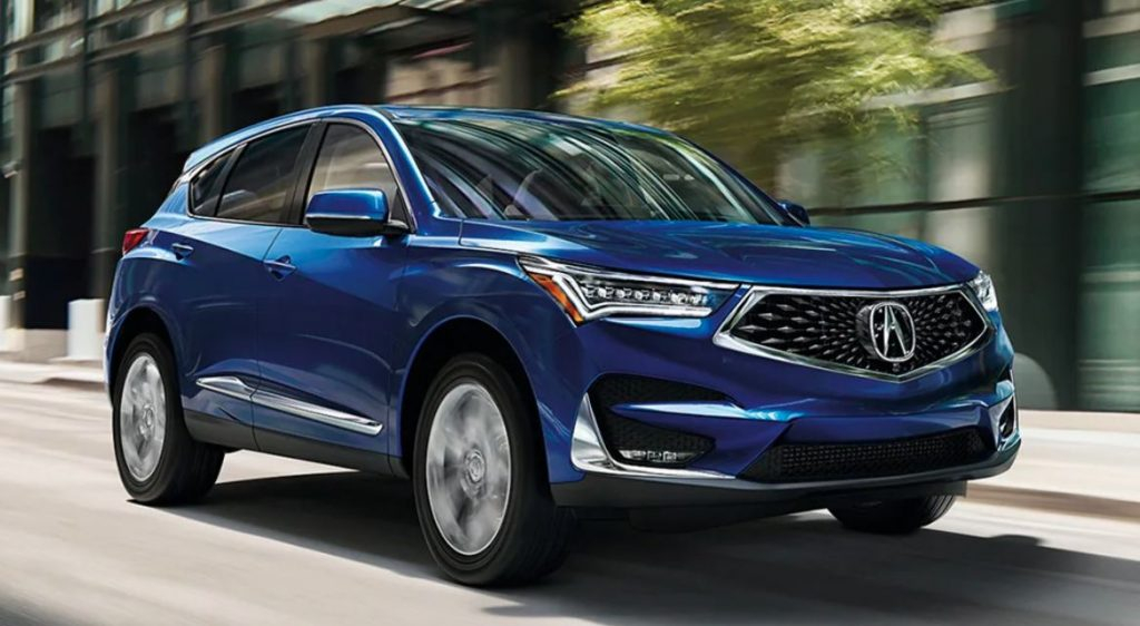 An Acura RDX, one of the safest midsize luxury SUVs, driving down a city street.
