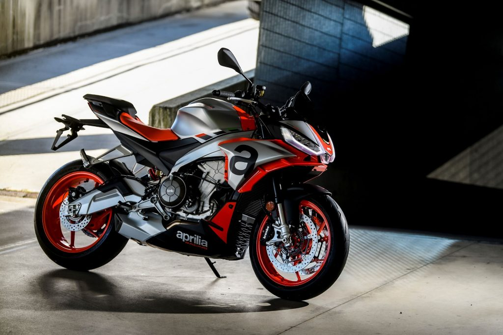 A silver-black-and-red 2021 Aprilia RS 660 parked by a concrete ramp