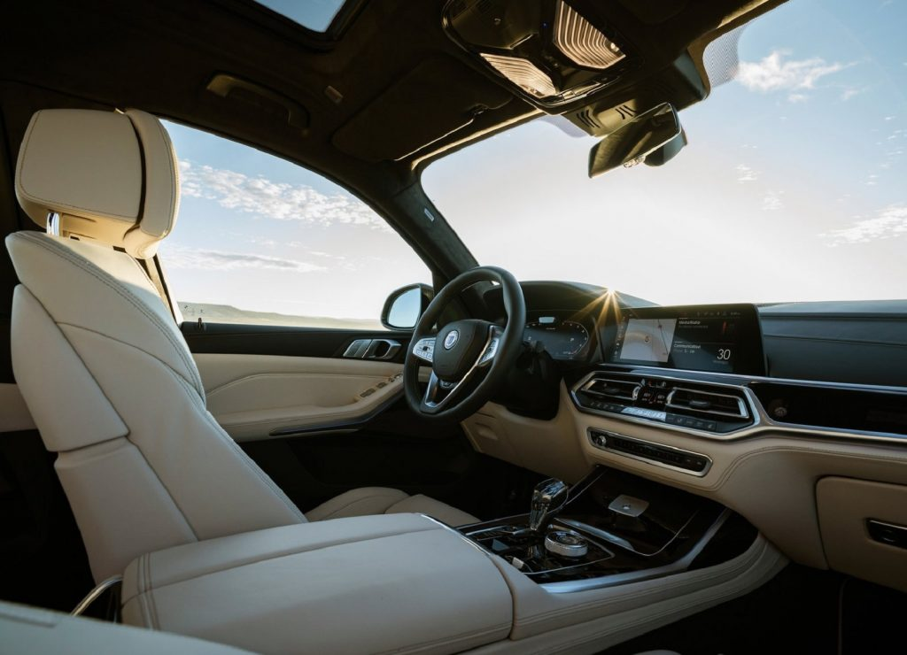 The tan-leather front seats and wood-trimmed dashboard of a 2021 BMW Alpina XB7
