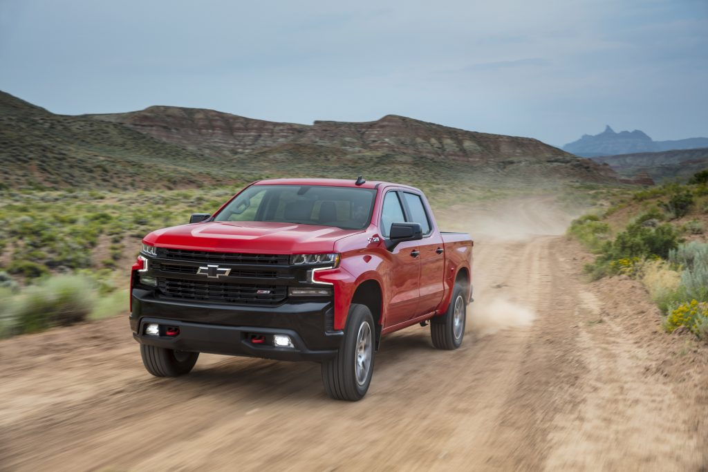 A red 2021 Chevy Silverado pickup truck driving on a dirt road