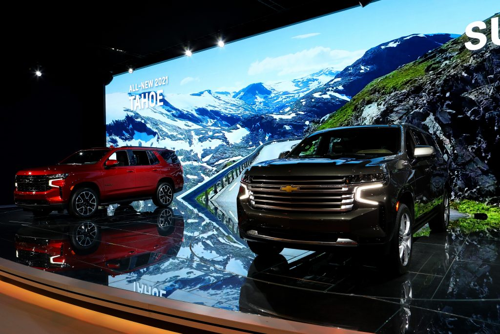 A red Chevrolet Tahoe and dark Suburban on display.