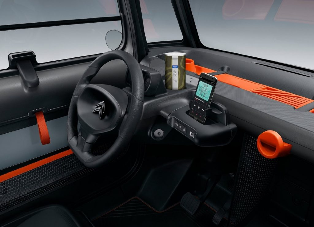 The black-and-orange dashboard and steering wheel of a 2021 Citroen Ami