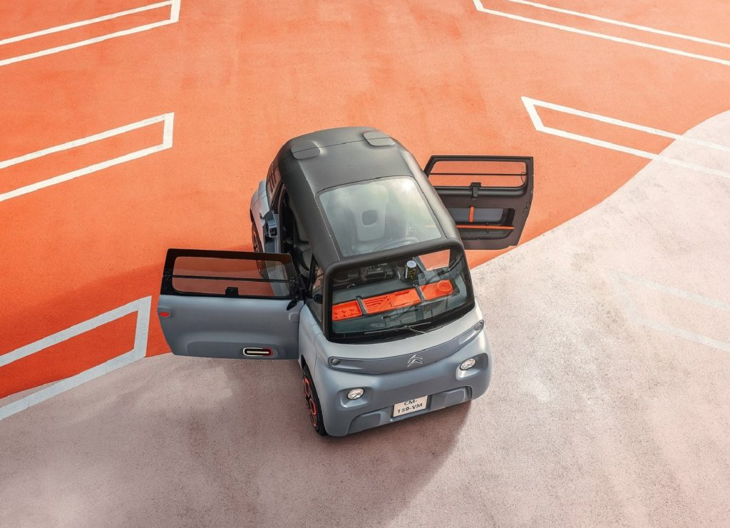 An overhead view of a gray 2021 Citroen Ami with its doors open on a gray-and-orange concrete surface