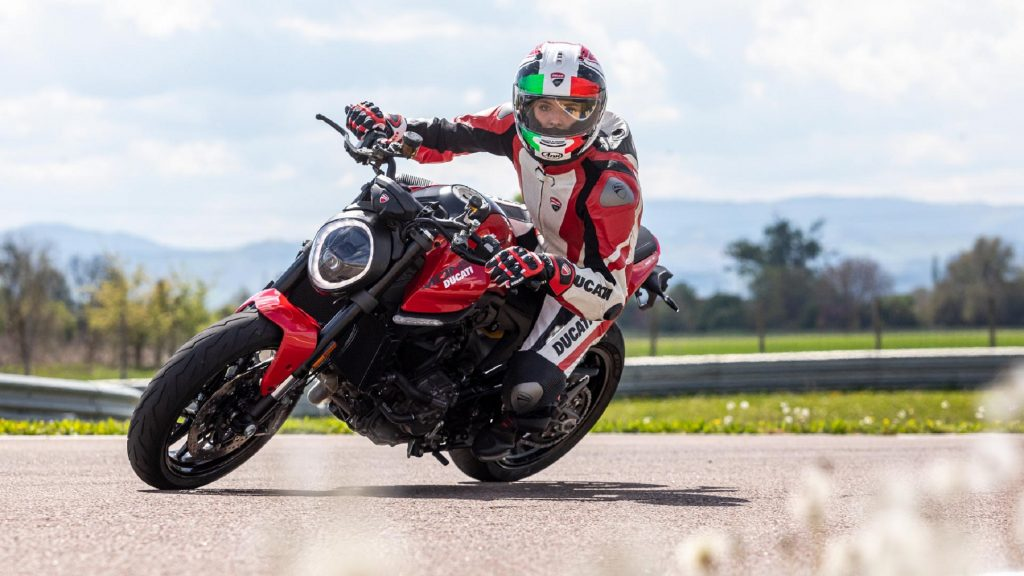 A red-and-white-clad rider takes a red 2021 Ducati Monster around the corner of a racetrack