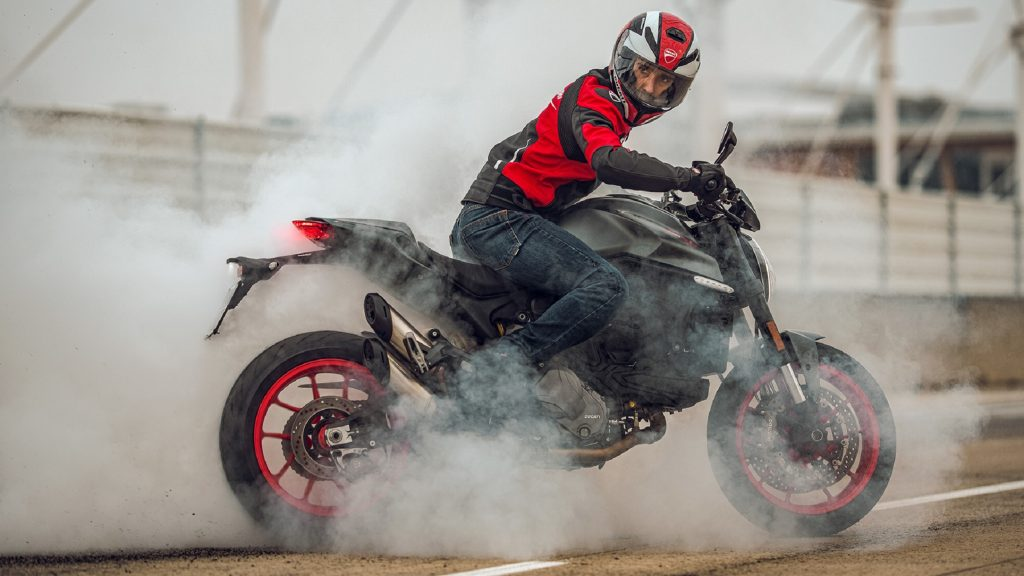 A red-clad rider on a gray 2021 Ducati Monster does a burnout on a racetrack