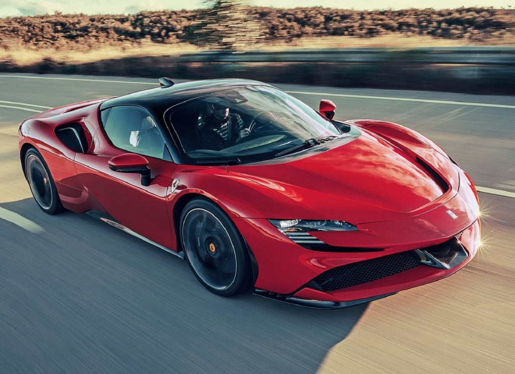 A red 2021 Ferrari SF90 Stradale driving down the highway