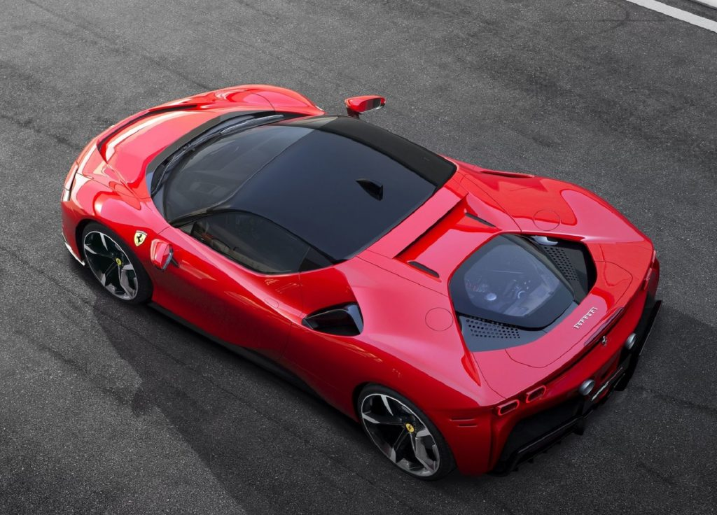 An overhead rear 3/4 view of a red 2021 Ferrari SF90 Stradale on a racetrack