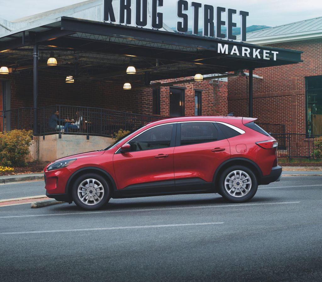 A red 2021 Ford Escape Hybrid parked in front of a market