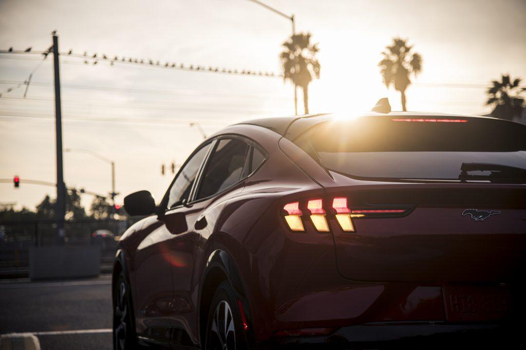 Une vue arrière d'un SUV électrique Ford Mustang Mach-E 2021 rouge s'est arrêté dans une rue bordée de palmiers alors que le soleil plane à l'horizon