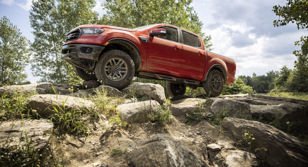 a red 2021 Ford Ranger pickup truck crawling up rocks