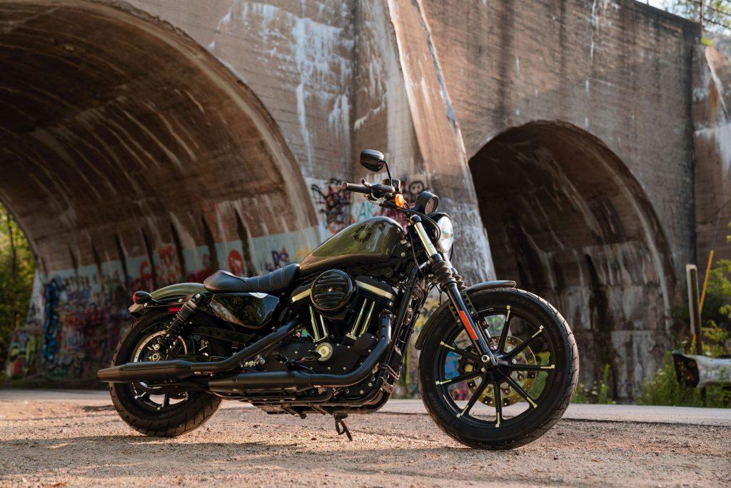 An olive-green 2021 Harley-Davidson Iron 883 Sportster next to a concrete bridge