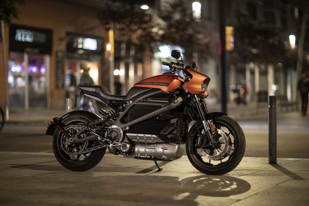An orange-and-black 2021 Harley-Davidson LiveWire parked on a city street at night