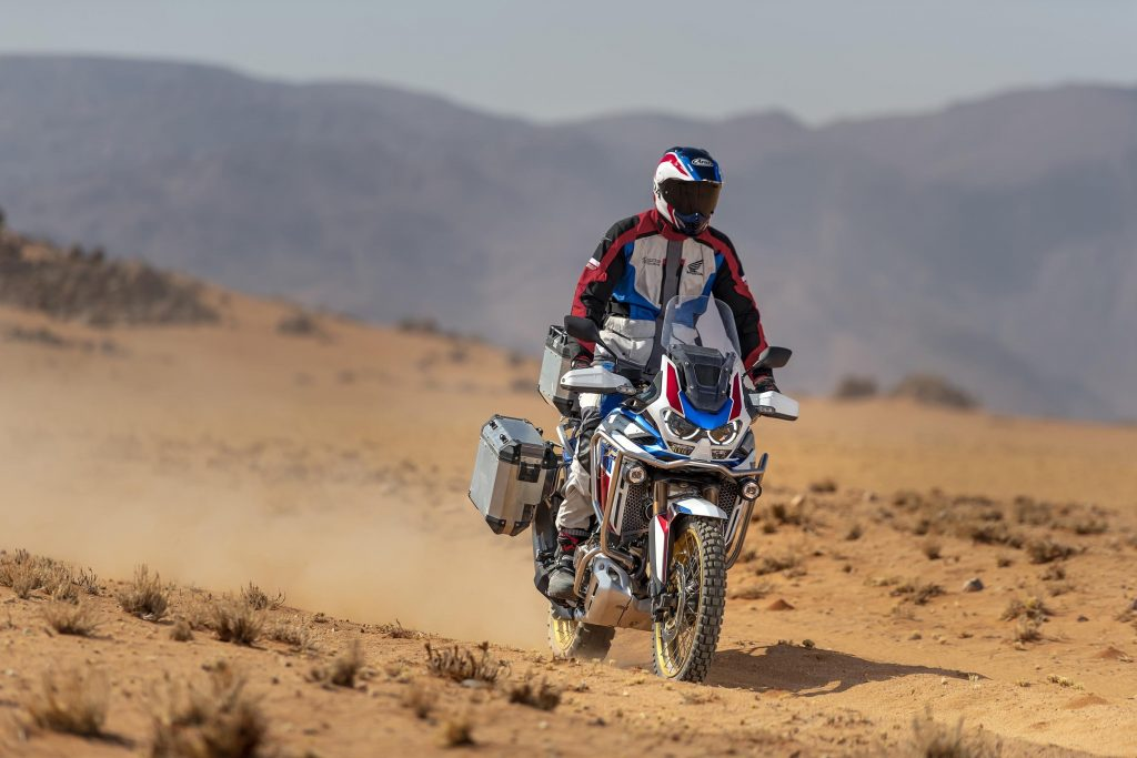 A white-red-and-blue-clad rider takes a white-red-and-blue 2021 Honda Africa Twin DCT through the desert