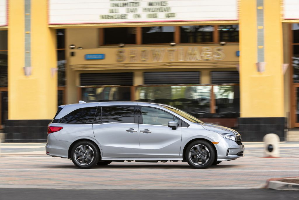 A silver 2021 Honda Odyssey parked in front of a movie theater