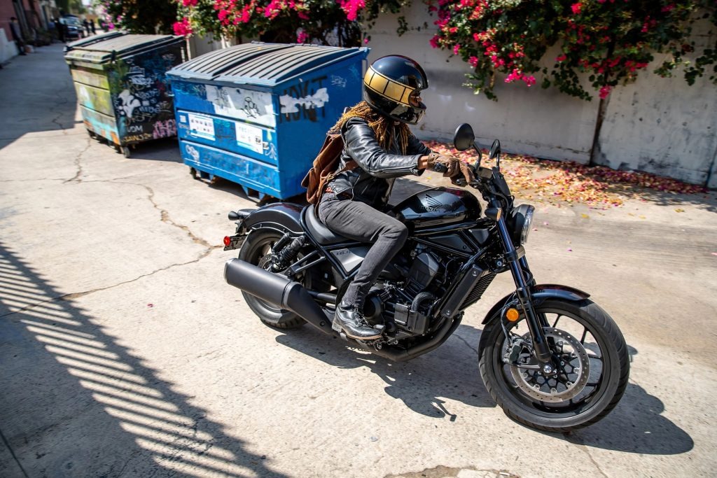 A rider with a black-and-gold helmet takes a black 2021 Honda Rebel 1100 DCT through an alleyway