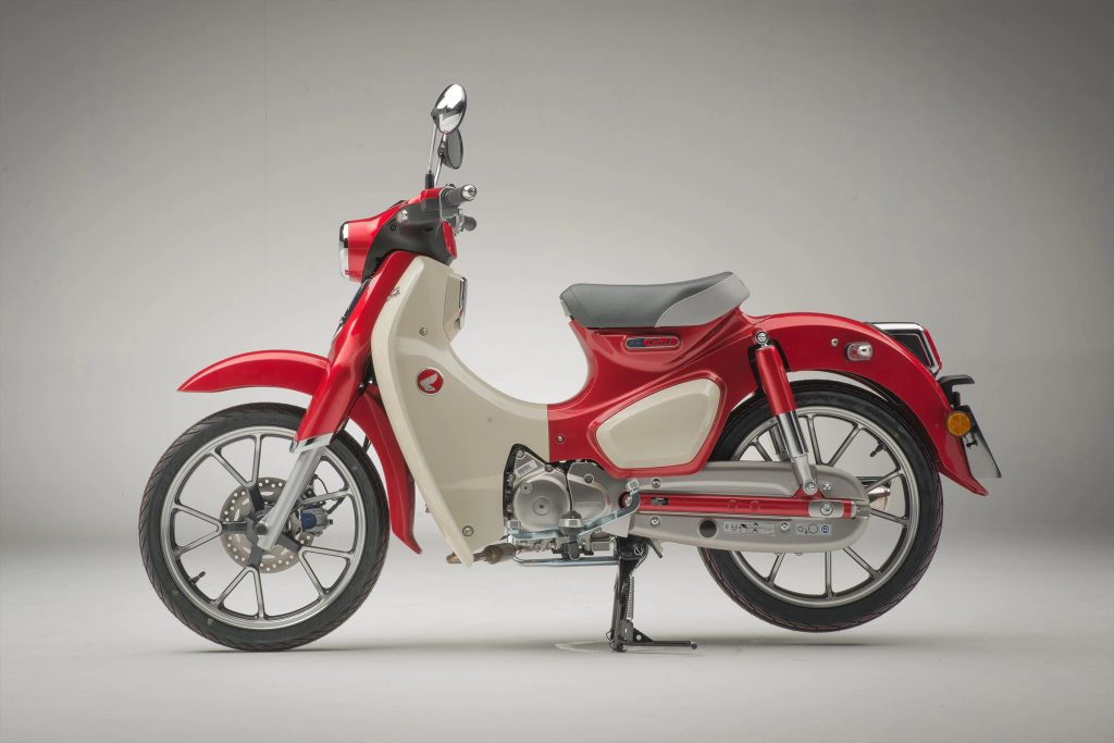The side view of a red-and-white 2021 Honda Super Cub C125 ABS