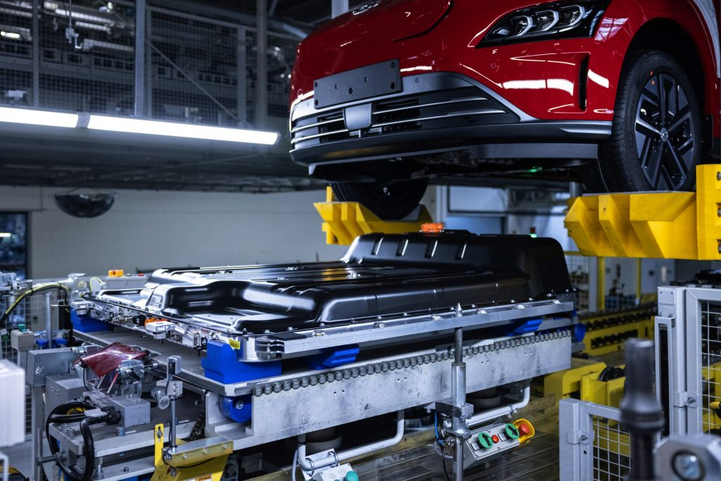 A red 2021 Hyundai Kona Electric body meets its battery pack during factory assembly
