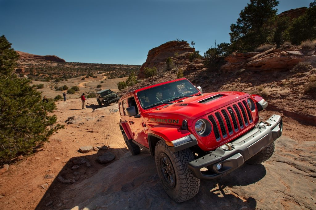 A red 2021 Jeep Wrangler Rubicon 392 SUV traveling on rocky terrain