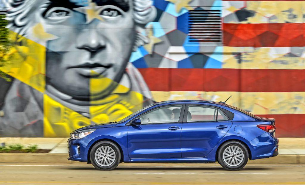 A blue 2021 Kia Rio driving past a mural