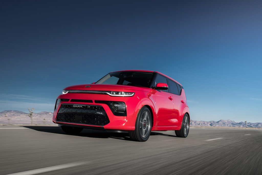 A red 2021 Kia Soul driving at speed on an open desert road with mountains in the background