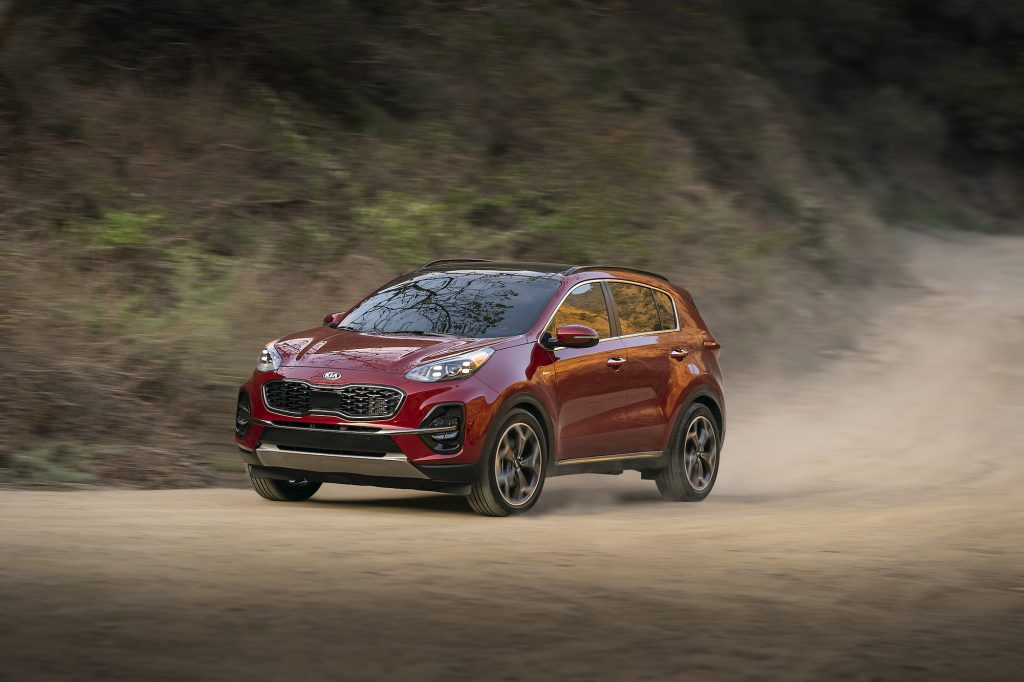 A red 2021 Kia Sportage compact SUV traveling on a dusty mountain road has better resale value than many other crossover models.