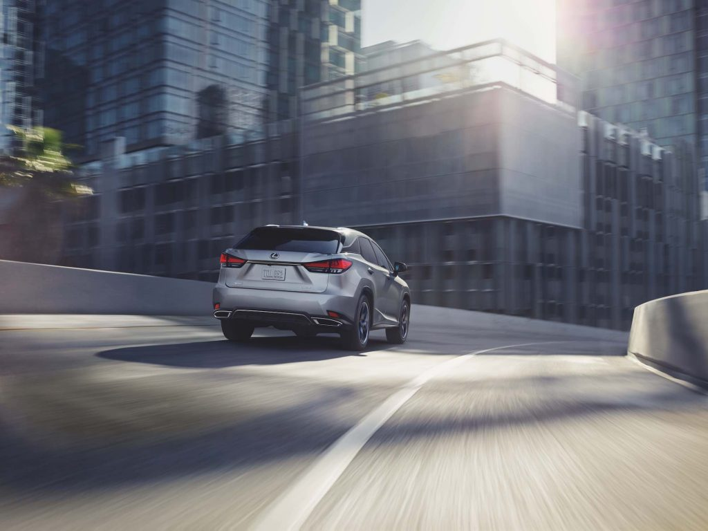 A silver 2021 Lexus RX midsize luxury SUV traveling on a highway ramp in a city