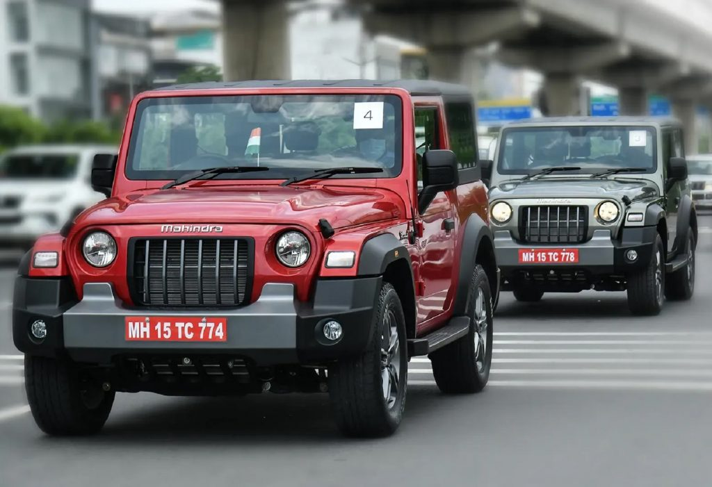 A red 2021 Mahindra Thar driving in front of a gray 2021 Mahindra Thar on an Indian city road