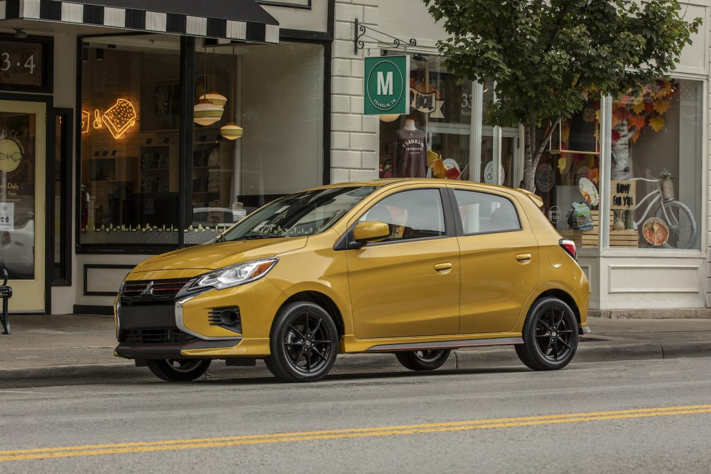 An orange 2021 Mitsubishi Mirage parked on a city street, one of the best affordable new cars under $20,000