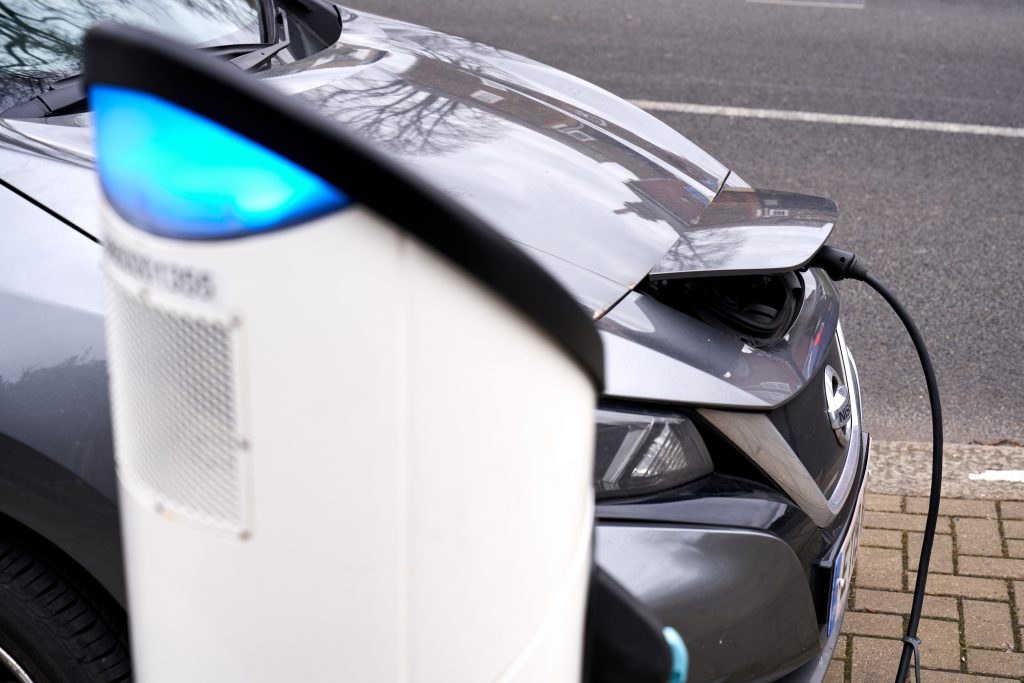 A gray 2021 Nissan Leaf EV sedan at a sharging station