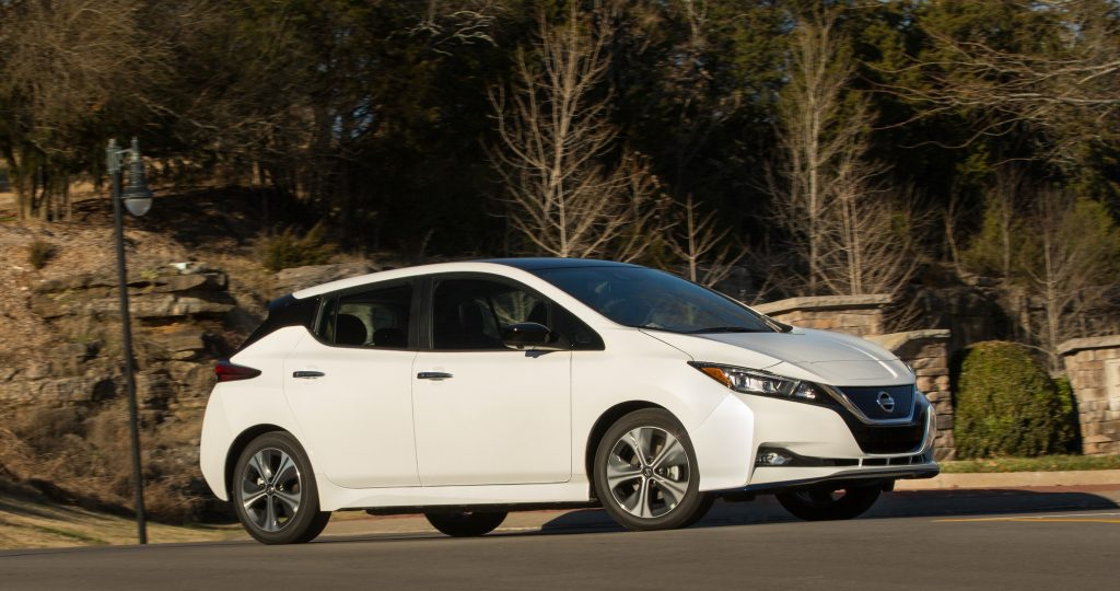 a white 2021 Nissan Leaf driving on a street shows the only mainstream vehicle on the list of models with the worst resale value.