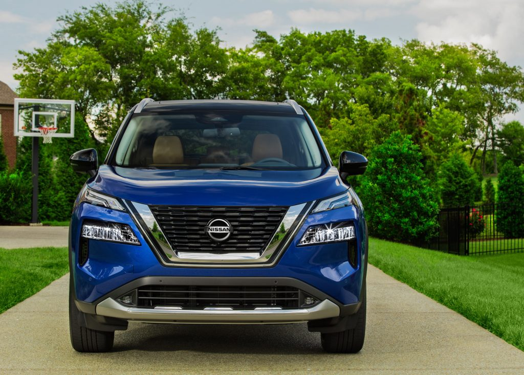 A blue 2021 Nissan Rogue parked in a suburban driveway with a basketball hoop