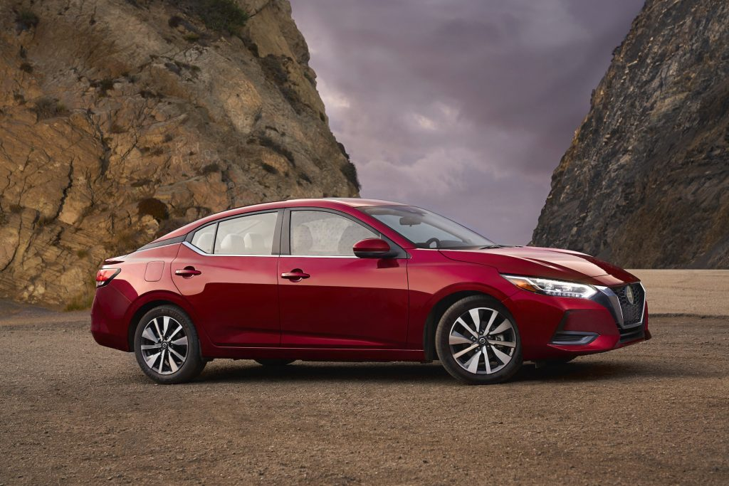 A red 2021 Nissan Sentra compact sedan parked between two mountains in front of dark clouds