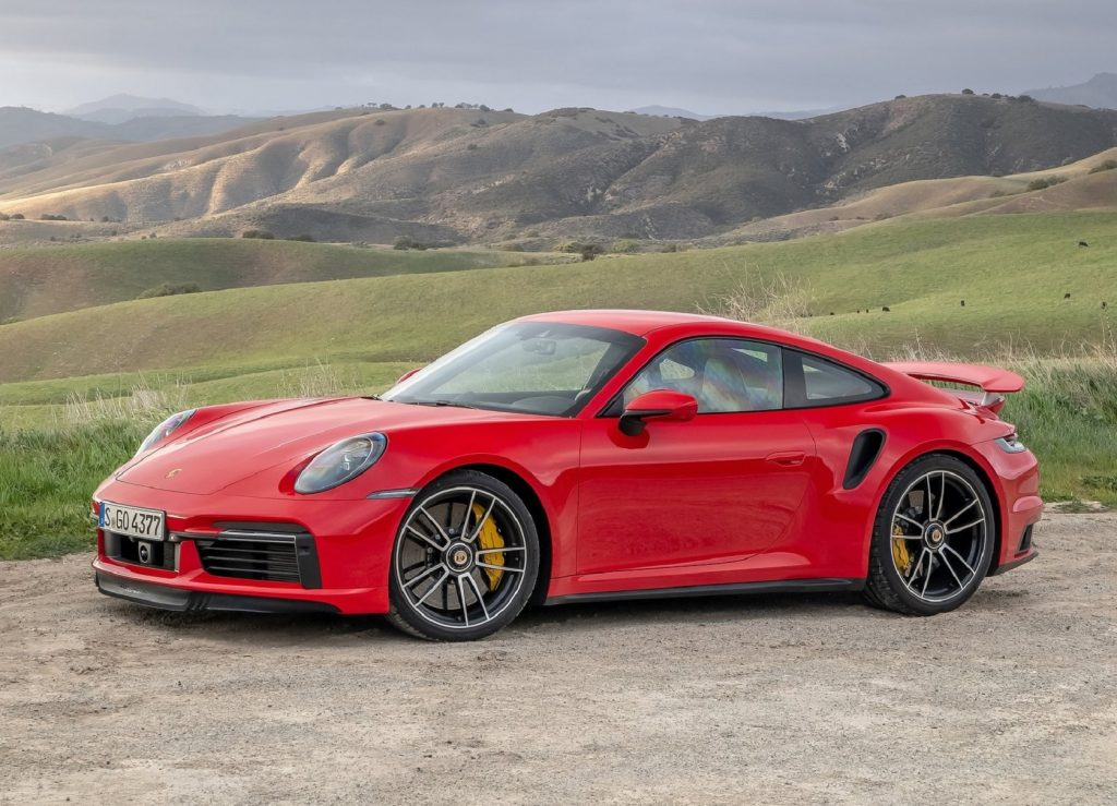 A red 2021 Porsche 911 Turbo S parked on a dirt parking space by rolling green hills