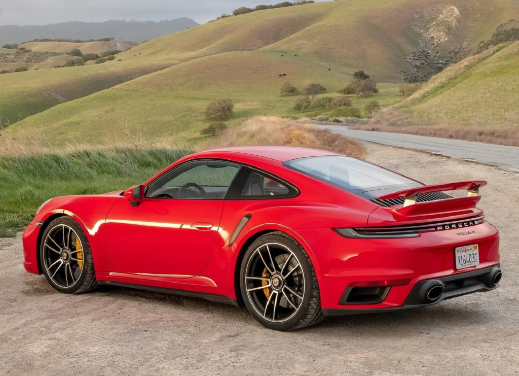 The rear 3/4 view of a red 2021 Porsche 911 Turbo S parked by a road through rolling green hills