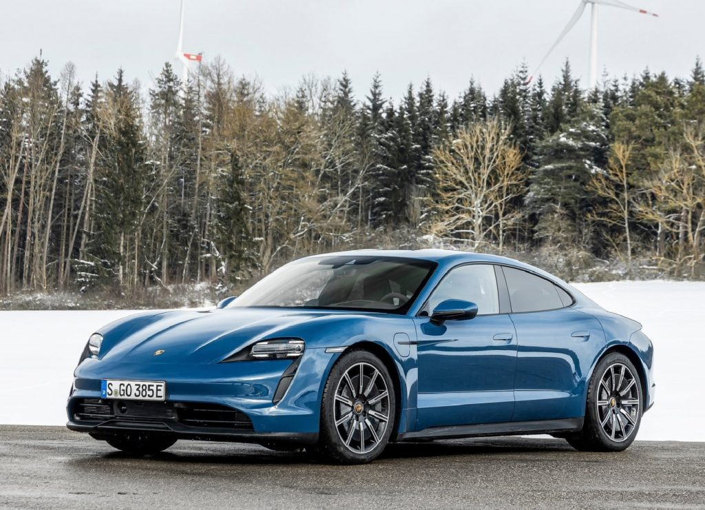 A blue 2021 Porsche Taycan in front of a snowy forest-lined field with a windmill in the background
