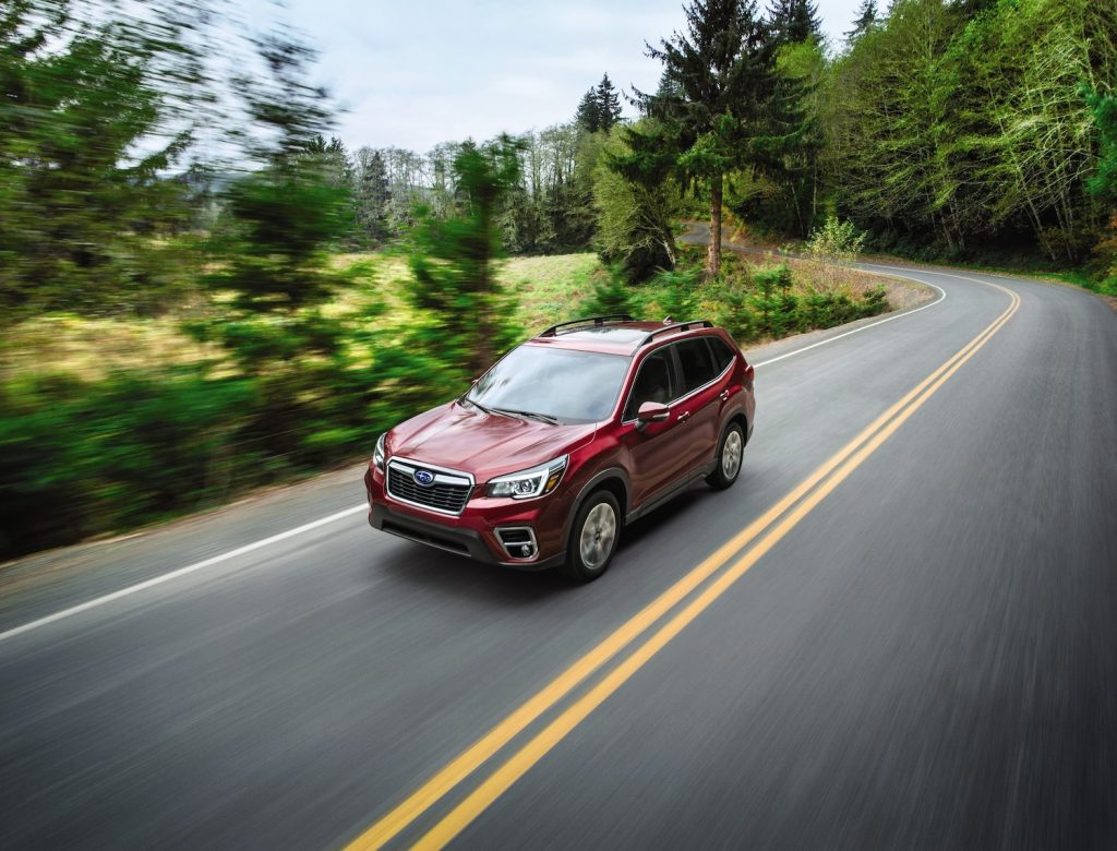 A red 2021 Subaru Forester compact SUV driving down an empty tree-lined street