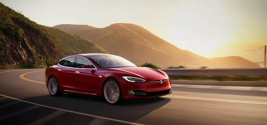 A red Tesla Model S driving