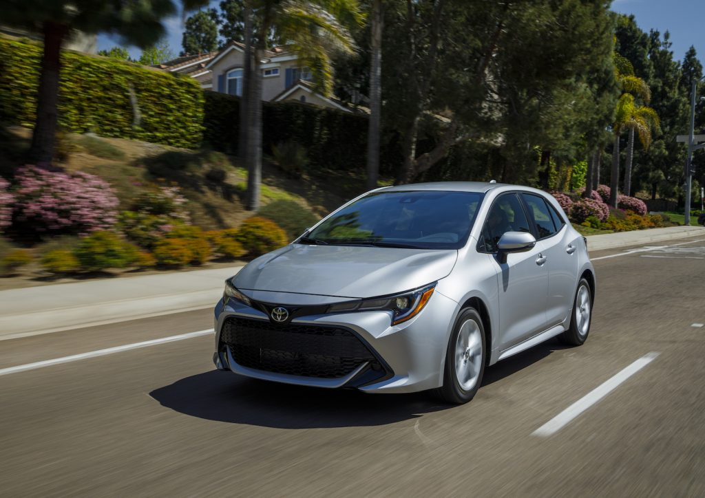 A silver 2021 Toyota Corolla Hatchback driving