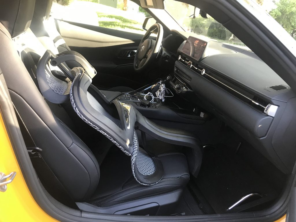 The top half of an office chair in the front seat of the Supra