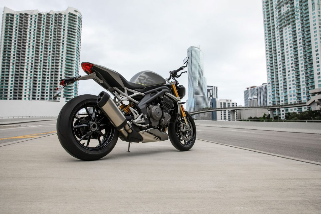 The rear 3/4 view of a gray-and-black 2021 Triumph Speed Triple 1200 RS on a city street