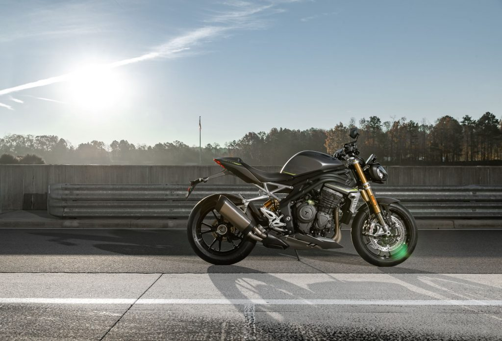 The side view of a gray-and-black 2021 Triumph Speed Triple 1200 RS on a racetrack