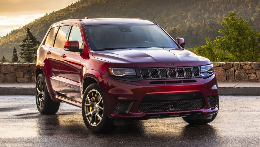 A red 2021 Jeep Grand Cherokee Trackhawk parked in front of the sunset