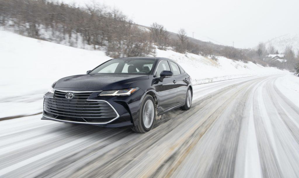 A Black 2021 Toyota Avalon hybrid driving through snow