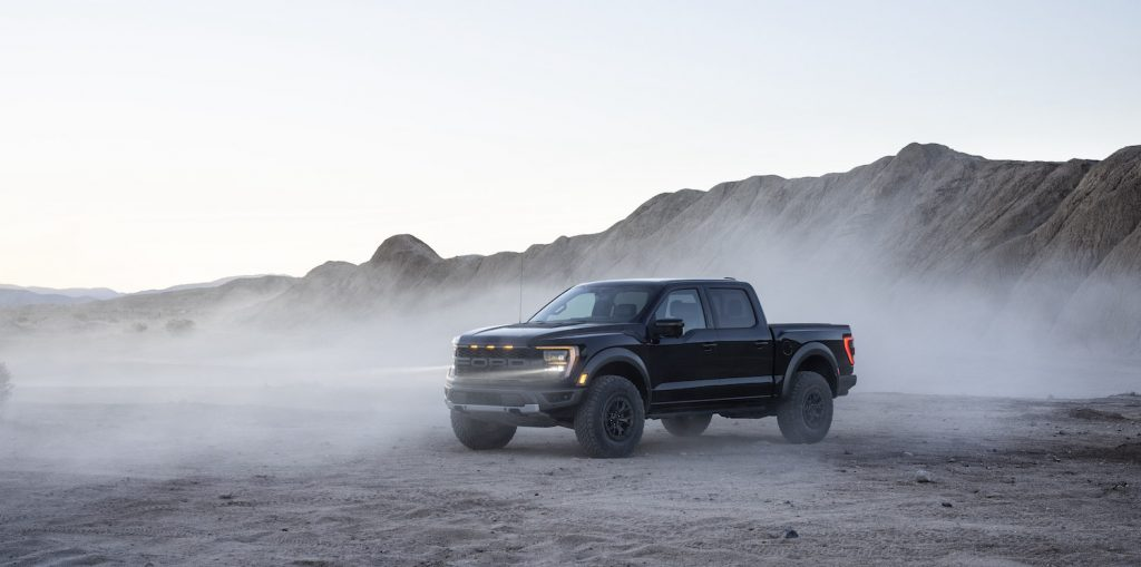 A Black 2021 Ford Raptor parked in the dust