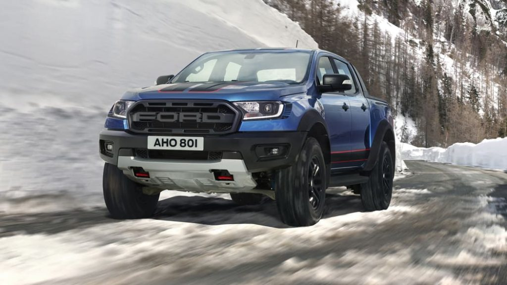 A blue 2021 Ford Ranger Raptor driving in snow