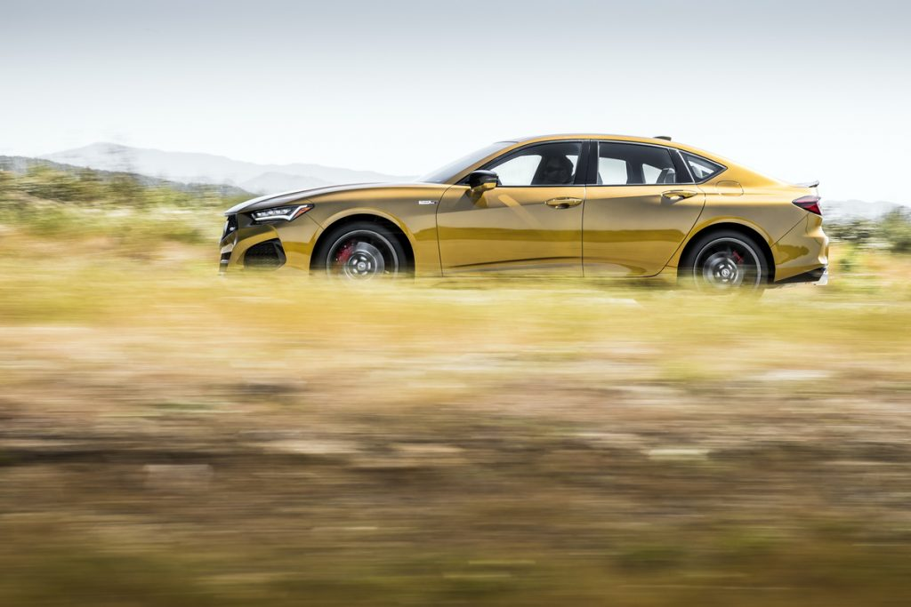 A gold TLX Type S flies by with a blurred foreground and background